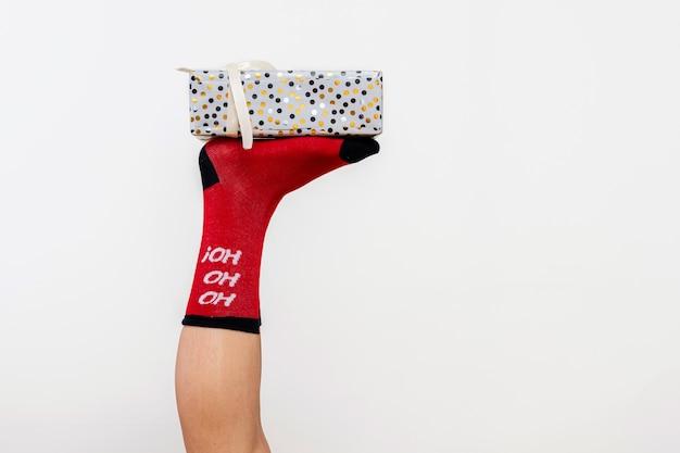 Szczupłe nogi kobiety w czerwonych pończochach boże narodzenie z pudełkiem na białym tle na biały, zbliżenie
