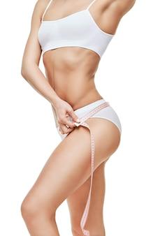 Szczupłe, opalone ciało kobiety na białym tle - obwód talii.