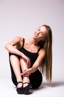 Szczupłe, opalone, sportowe ciało kobiety na szarej ścianie
