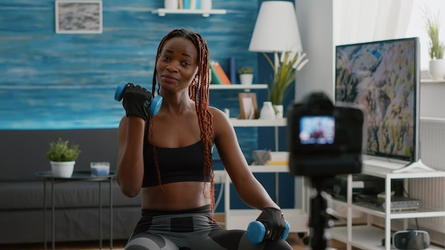 Szczupły czarny trener robi poranne ćwiczenia jogi, siedząc na szwajcarską piłkę fitness w salonie, nagrywając trening aerobowy przy użyciu hantli filmowania samouczka pilates. dopasuj kobiety pracujące na mięśnie ciała