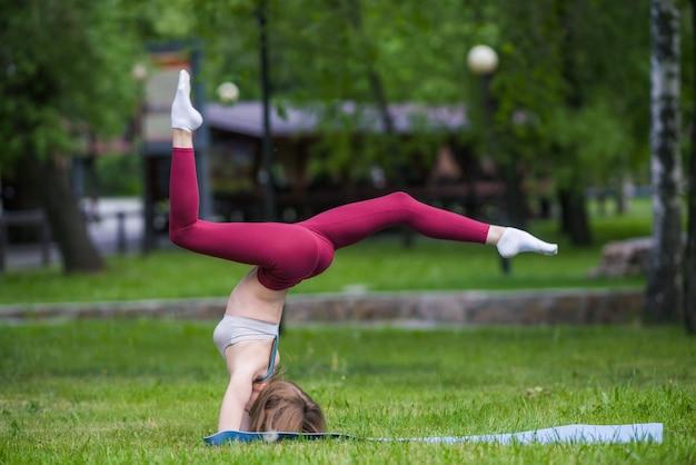 Szczupły młody brunetka kobieta jogin robi trudne ćwiczenia jogi na zielonej trawie