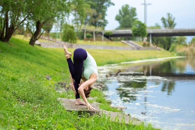 Szczupły młody jogin brunetka nie wykonuje żadnych skomplikowanych ćwiczeń jogi na zielonej trawie latem wbrew naturze