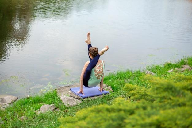 Szczupły młody jogin brunetka wykonuje trudne ćwiczenia jogi na zielonej trawie