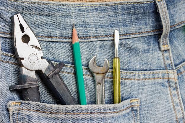 Szczypce i inne narzędzia robocze w kieszeni dżinsów.