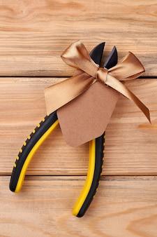 Szczypce ozdobione kokardką. narzędzie na drewnianym tle. prezent dla prawdziwego mężczyzny.