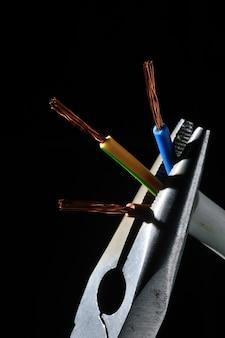 Szczypce trzymają pozbawione izolacji przewody elektryczne. na czarnym tle. zbliżenie.