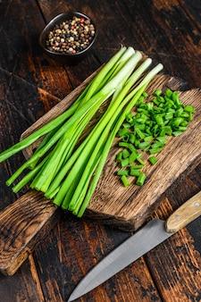 Szczypiorek zielonej cebuli pokroić na desce do krojenia. ciemne tło drewniane. widok z góry.