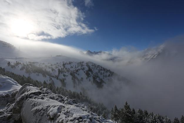 Szczyt gór z lasem pokrytym śniegiem, mgłą i chmurami w słoneczny mroźny dzień