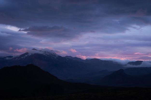 Szczyt górski ze śniegiem i chmurami podczas dramatycznego i kolorowego zachodu słońca na szlaku turystycznym laugavegur w pobliżu thorsmork.