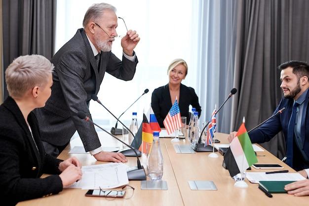 Szczyt polityczny przedstawicieli różnych krajów i dyskusja na tematy międzynarodowe, spotkanie bez więzi. w nowoczesnej, jasnej sali konferencyjnej