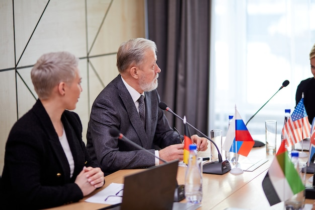 Szczyt polityczny przedstawicieli różnych krajów i dyskusja w sprawach międzynarodowych, spotkanie bez więzi. w nowoczesnej, jasnej sali konferencyjnej