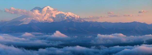 Szczyty elbrusu na kaukazie wczesnym rankiem ponad chmurami