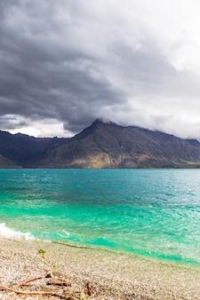 Szczyty górskie aż do chmur nad turkusową wodą jezioro wakatipu w nowej zelandii