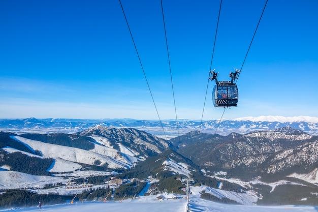 Szczyty zimowych gór. słoneczna pogoda. kabina wyciągu narciarskiego na tle błękitnego nieba. stoki narciarskie poniżej