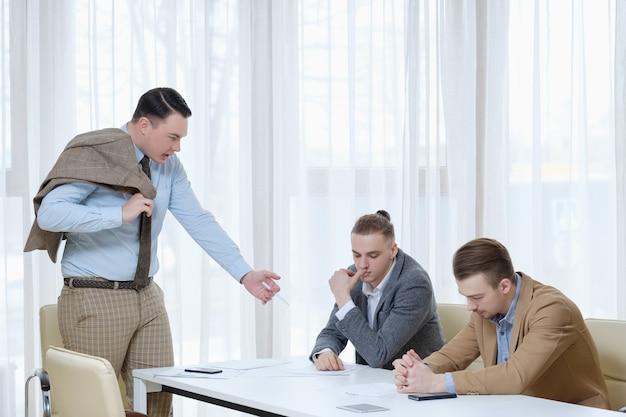 Szef beszta swoich pracowników. biznesmenów otrzymuje naganę i upomnienie od głównego menedżera.