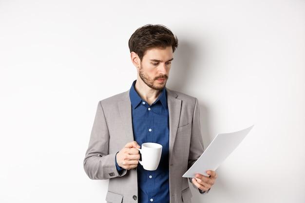 Szef czytający dokumenty i pijący poranną kawę z kubka, patrząc na papier poważny, stojący w garniturze na białym tle.