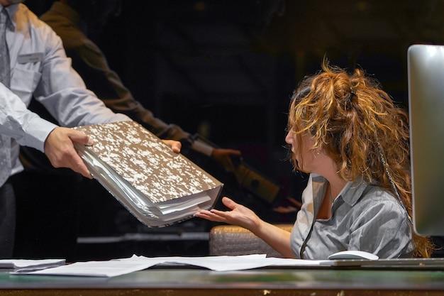Szef daje zapracowaną menadżerkę paczkę dokumentów
