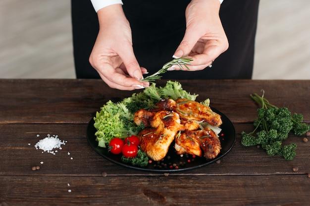 Szef dekorujący pikantne danie ze skrzydełkami kurczaka