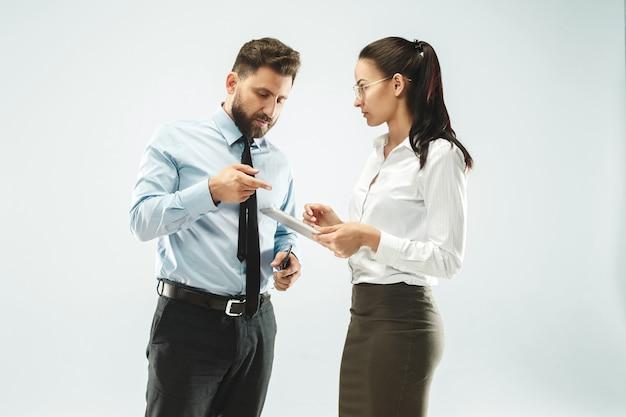 Szef i jego sekretarka stojąca w biurze lub pracowni.