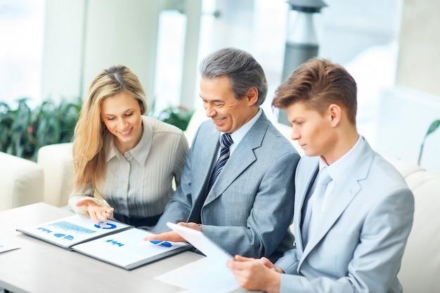 Szef i jego zespół biznesowy omawiają wykres finansowy