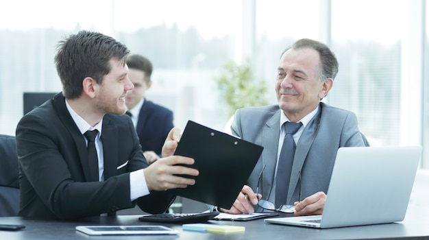 Szef i pracownik omawiający dokument siedzący przy biurku