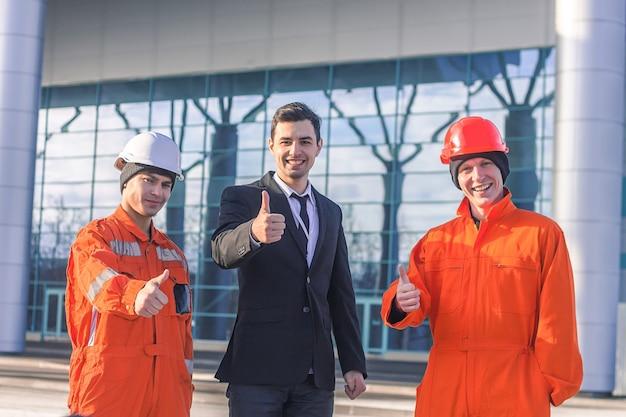 Szef i zespół młodych inżynierów pokazując kciuk do góry.