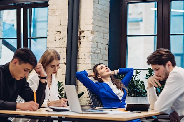 Szef interesu relaks, podczas gdy jej koledzy pracują przy stole w biurze