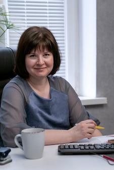 Szef kobieta pije kawę w miejscu pracy. przerwa na lunch. portret kobiety biznesu w gabinecie. uśmiechnięty administrator.
