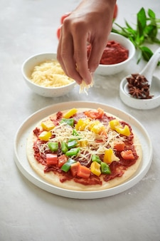 Szef krok po kroku robi ciasto na pizzę margarita i składniki do pizzy