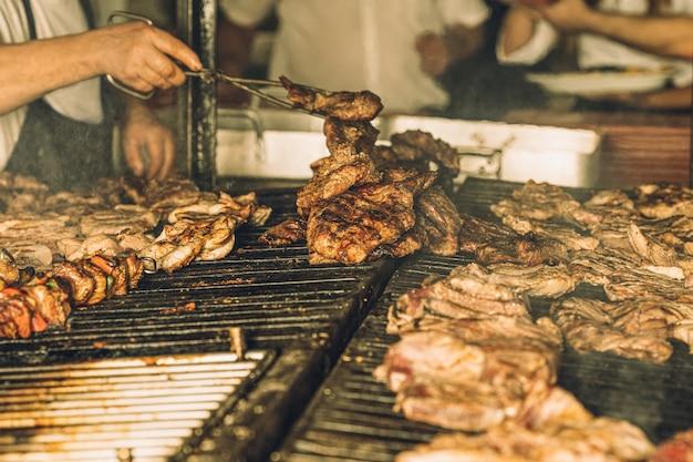 Szef kuchni bez twarzy przygotowujący i gotujący kawałki mięsa na grillu w restauracji.