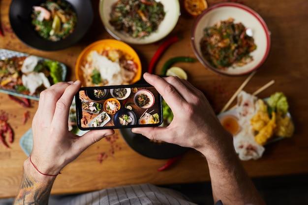 Szef kuchni biorąc zdjęcie kuchni azjatyckiej