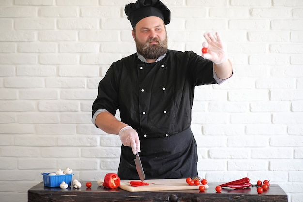 Szef kuchni brodaty przygotowuje posiłki przy stole w kuchni
