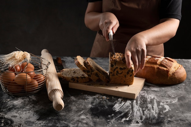 Szef kuchni cięcia bochenek chleba na desce do krojenia