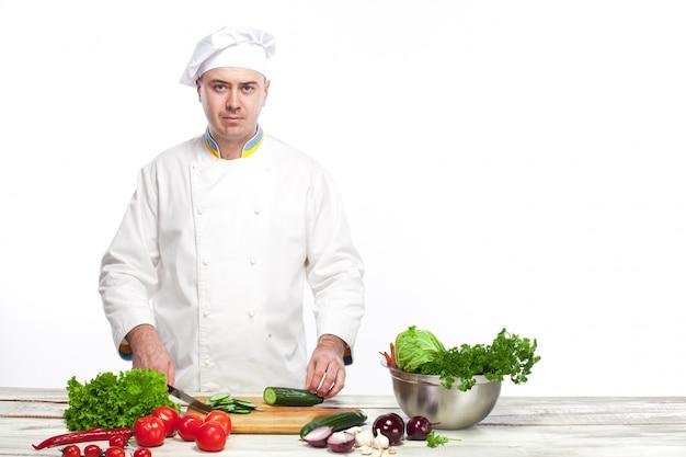 Szef kuchni cięcia zielonego ogórka w swojej kuchni