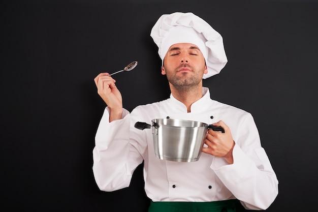 Szef kuchni cieszący się aromatem posiłku