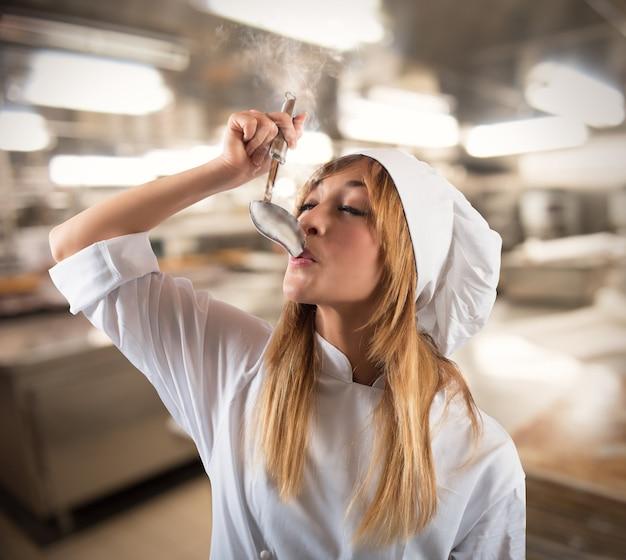 Szef Kuchni Degustuje Z Kadzi Parujące Jedzenie Premium Zdjęcia