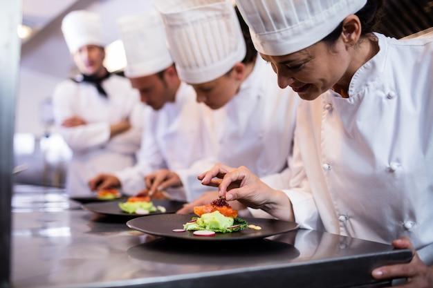Szef kuchni dekorujący talerz z jedzeniem