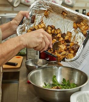 Szef kuchni dodaje do sałatki bakłażana pieczonego w piekarniku