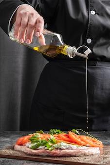 Szef kuchni dodaje olej do potrawy mięsnej