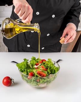 Szef kuchni dodaje olej do sałatki