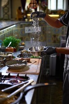 Szef kuchni dodaje parmezan, proces gotowania spaghetti z owocami morza