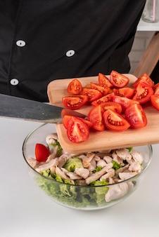Szef kuchni dodaje pomidory do sałatki mięsnej
