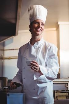 Szef kuchni dodaje przyprawy na patelni