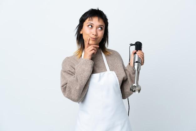 Szef kuchni dziewczyna używa ręki blender nad odosobnionym białym główkowaniem pomysł