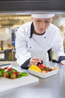 Szef kuchni garniruje owocowego kosz w kuchni