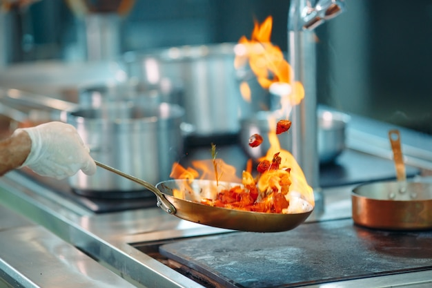 Szef kuchni gotowanie warzyw na patelni wok.