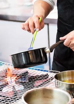 Szef kuchni gotuje jedzenie w kuchni, szef kuchni przygotowuje jedzenie