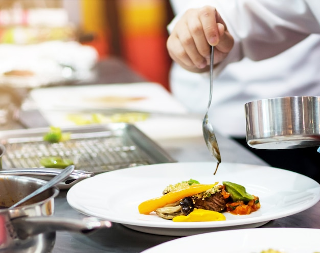 Szef kuchni gotuje jedzenie w kuchni, szef kuchni przygotowywa jedzenie