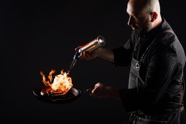 Szef kuchni gotuje kiełbasę, piecze klopsiki na otwartym ogniu
