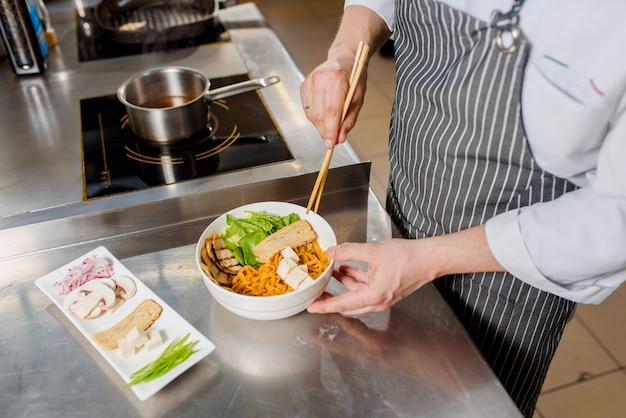 Szef kuchni gotuje makaron spaghetti do zupy ramen
